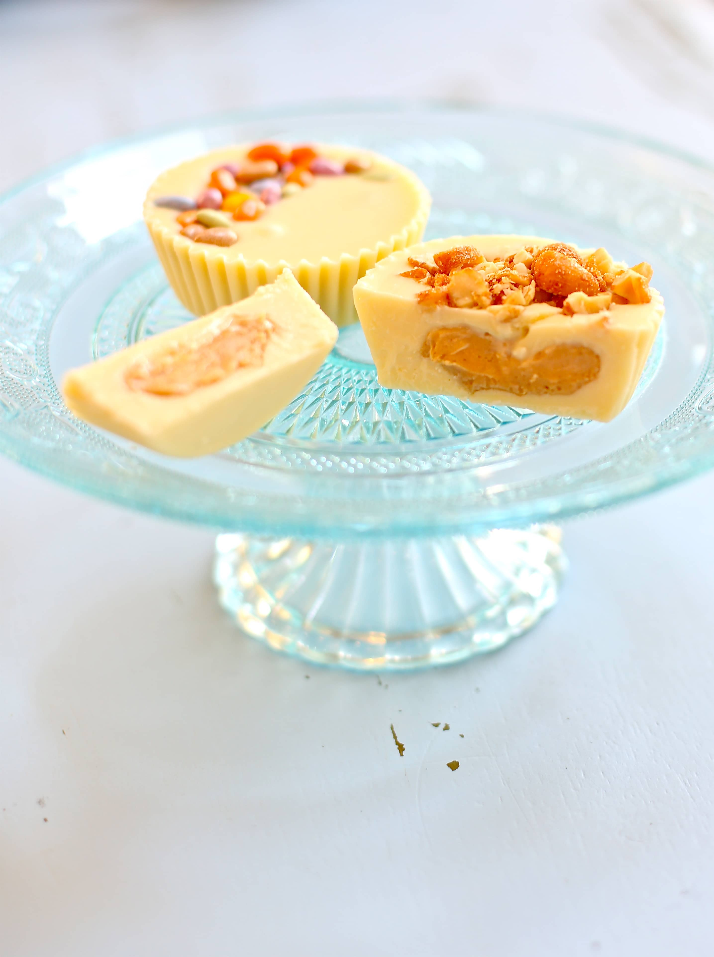 Two white chocolate peanut butter cups with candied and peanut topping served on a blue glass plate