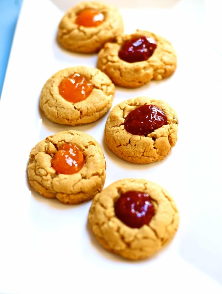 Peanut Butter and Jam Cookies with cherry and apricot jam on a white serving platter