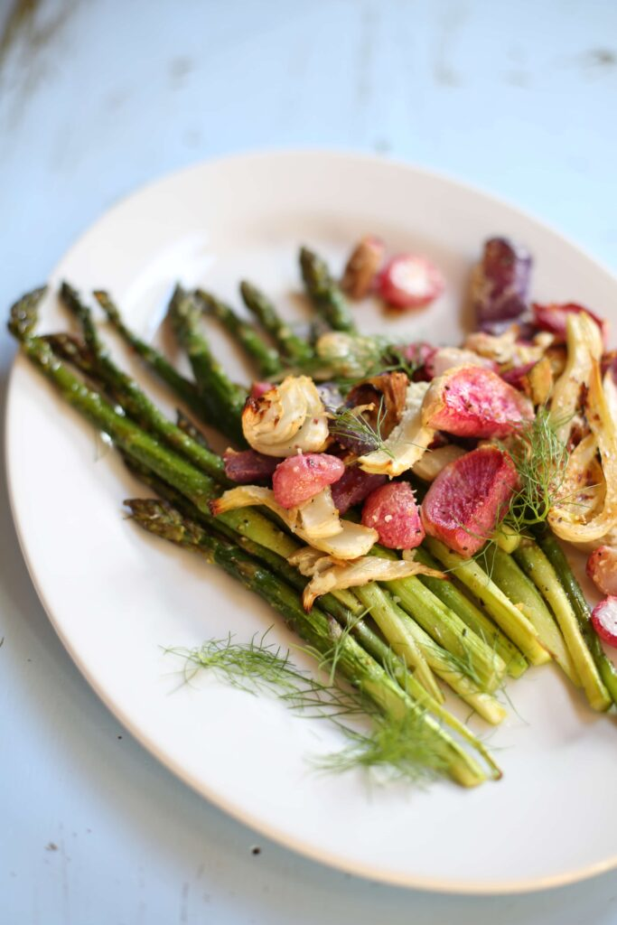 Asparagus fennel and radishes roasted and placed on a white plate on blue background