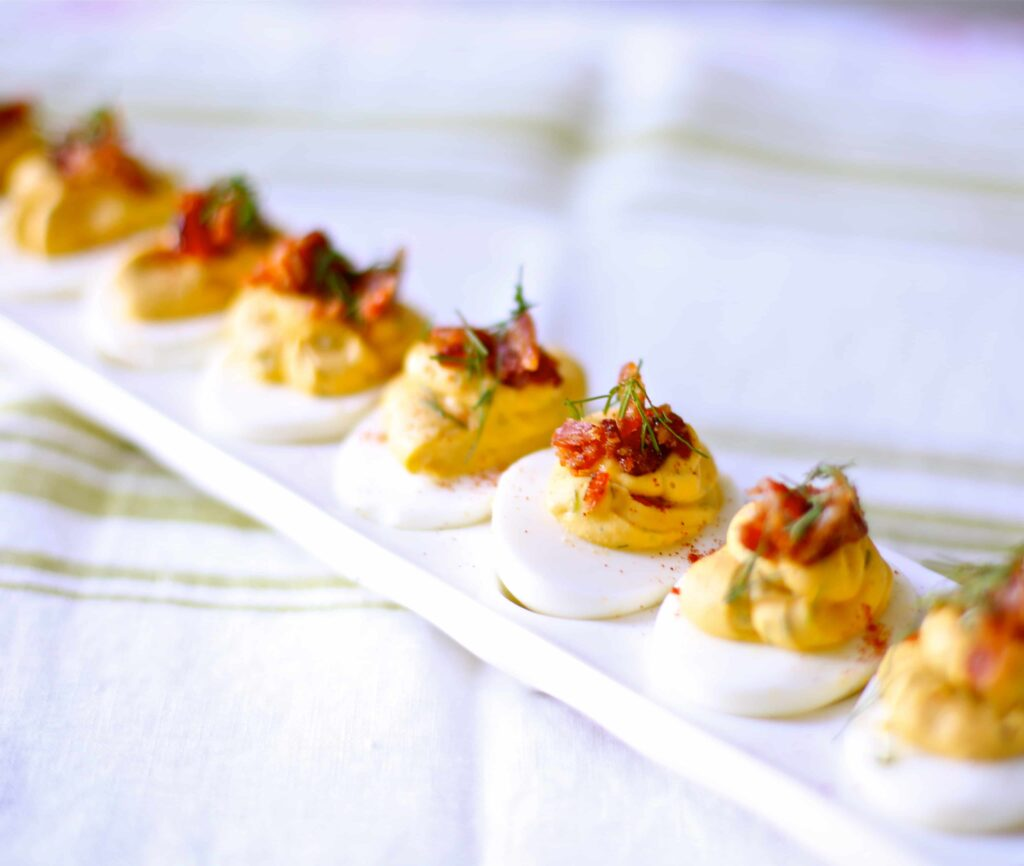 Deviled Eggs with Candied Bacon and Fresh Dill on a white tray