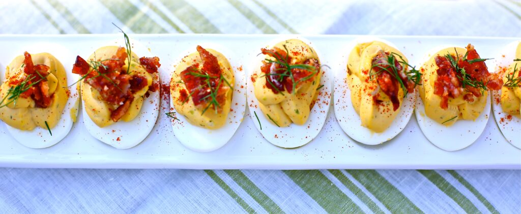 Deviled Eggs with Candied Bacon and Fresh Dill on a white tray on striped linen