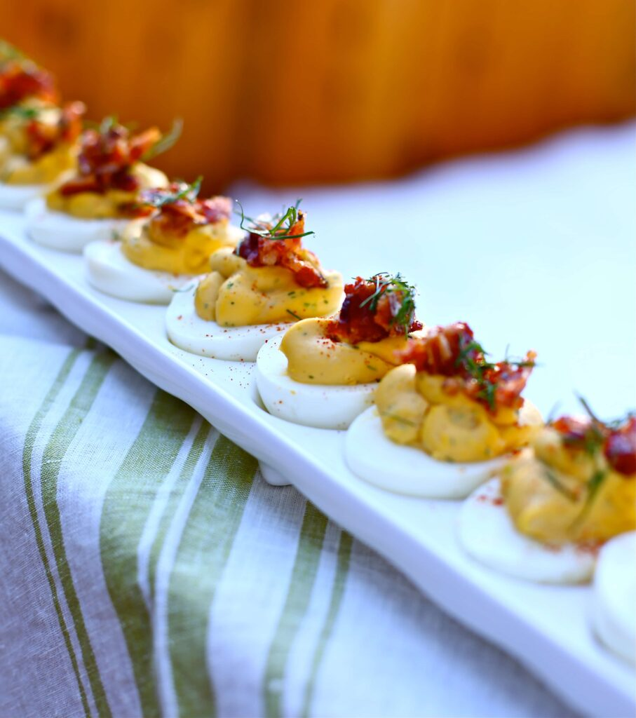 Deviled Eggs with Candied Bacon and Fresh Dill on ledge with striped linen