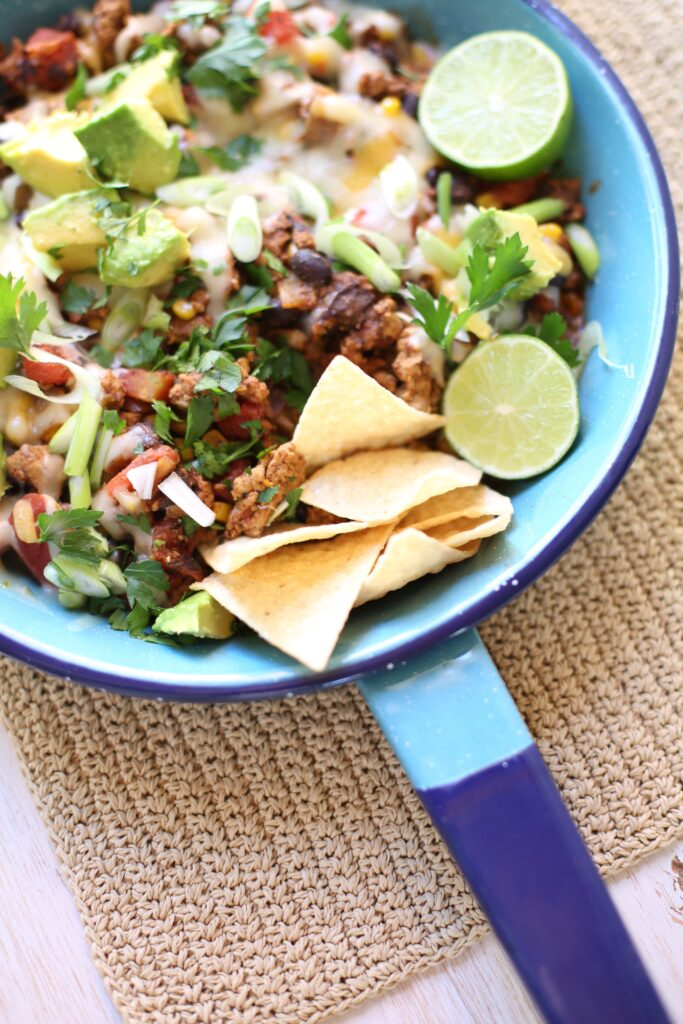 Taco Skillet Bake with chips and limes in a blue skillet pan