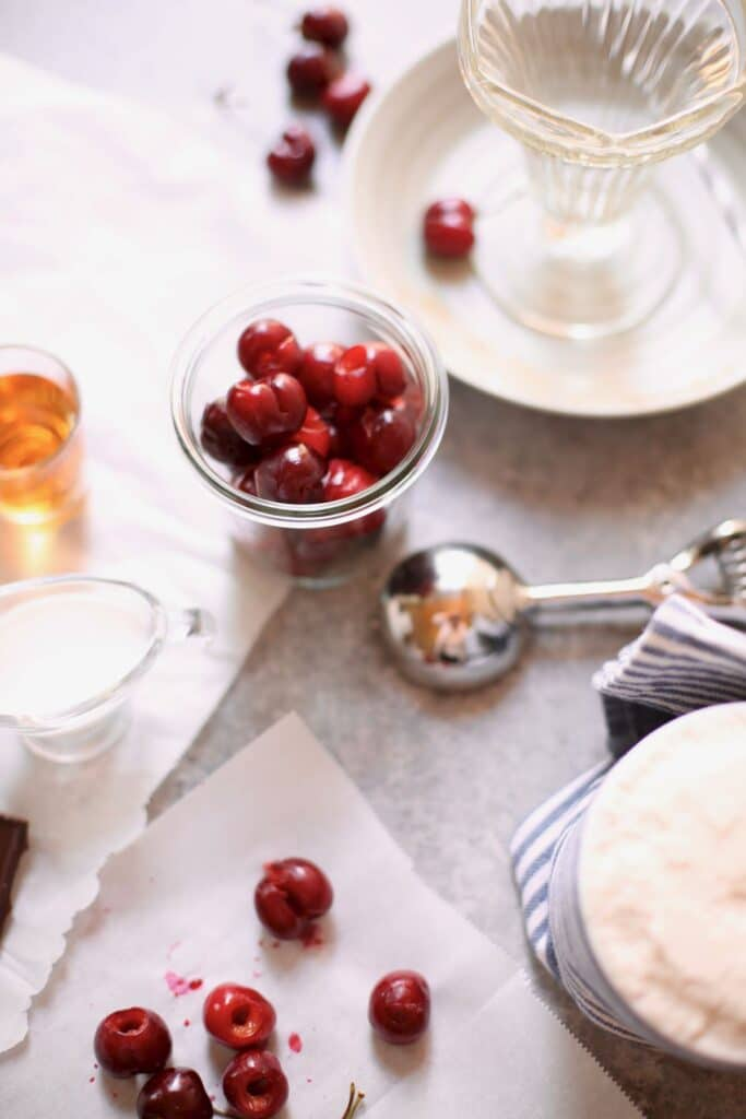 cherries and an ice cream scoop and cream on a gray table