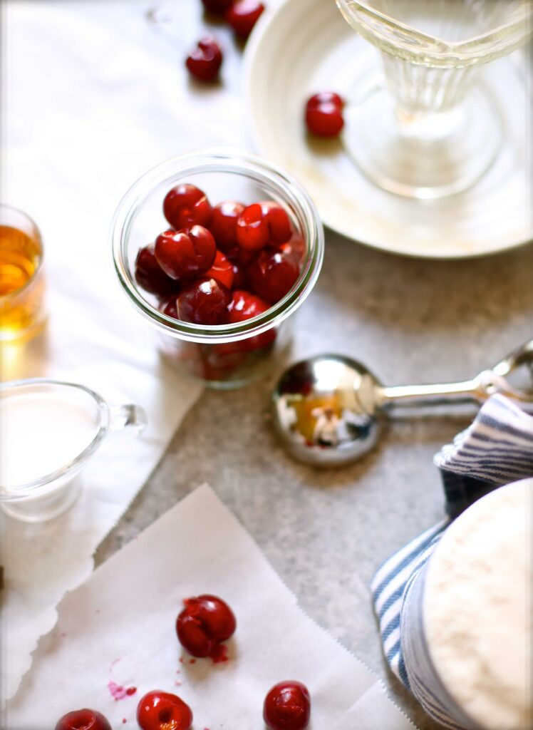 Fresh cherries in a small glass jar next to an ice cream scoop