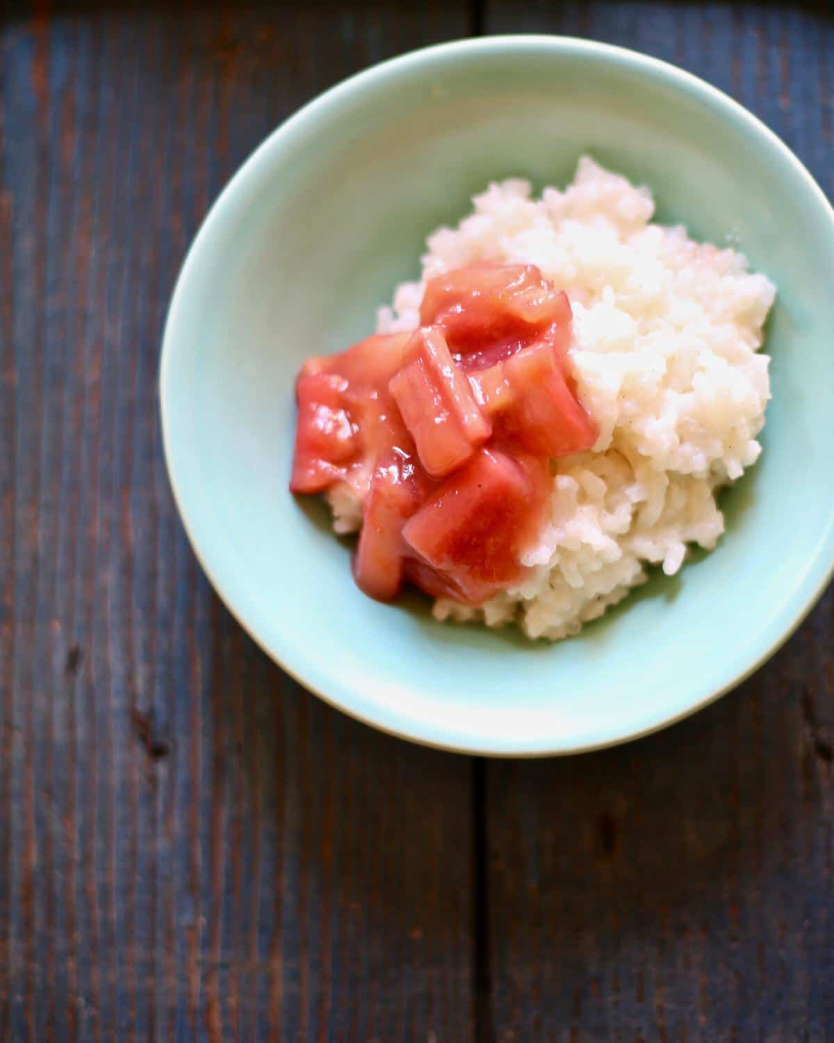 rice pudding with rhubarb in a small blue bowl on a table