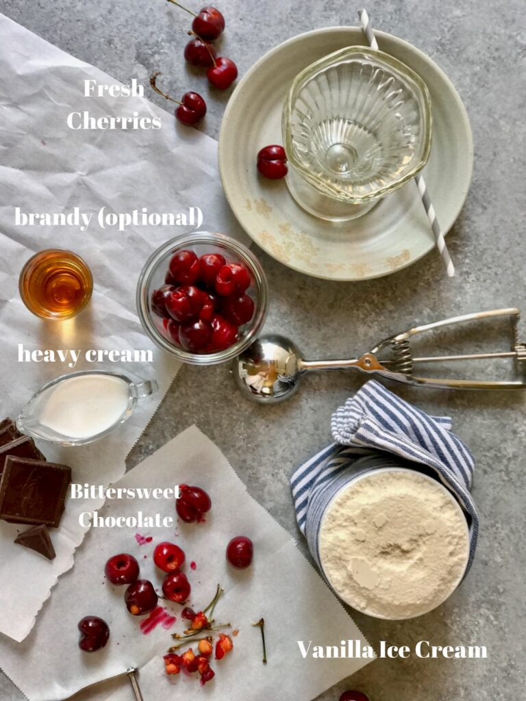 cherries, a glass, vanilla ice cream, booze and an ice cream scoop on a gray table