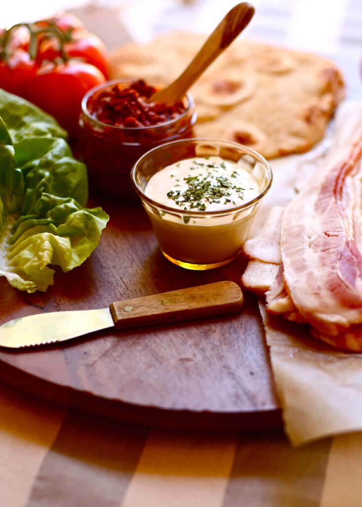 Mayonnaise, sun dried tomato pesto, naan bread, butter lettuce and bacon sit on a cutting board with knife