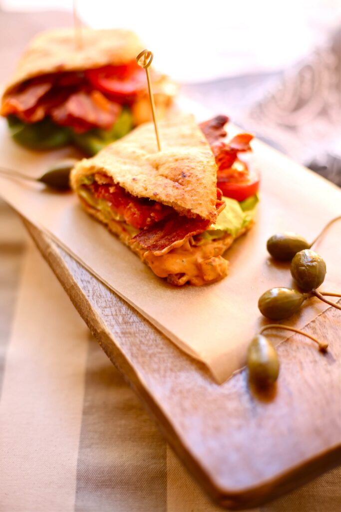 Naan BLT with Sun Dried Tomato Mayo on a cutting board with caper berries