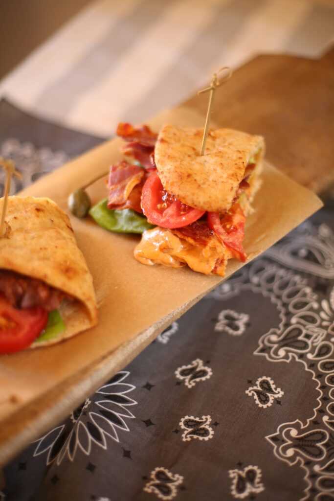 Naan BLT with Sun Dried Tomato Mayo, 2 pieces on a cutting board with gray bandana below it
