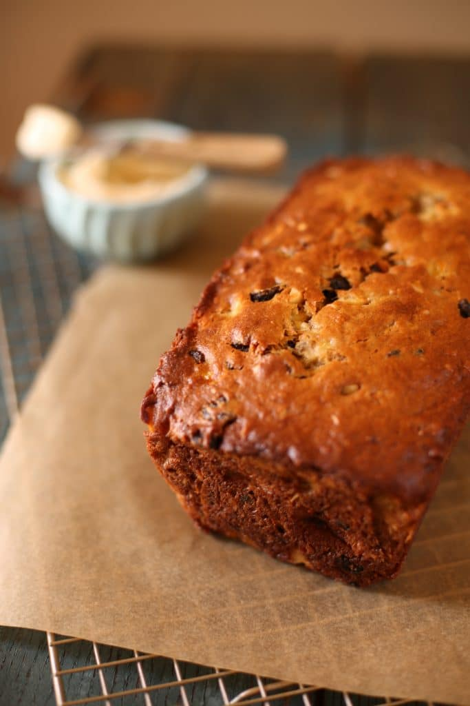 California Fig Banana Bread cooling on a rack with cream cheese frosting behind it