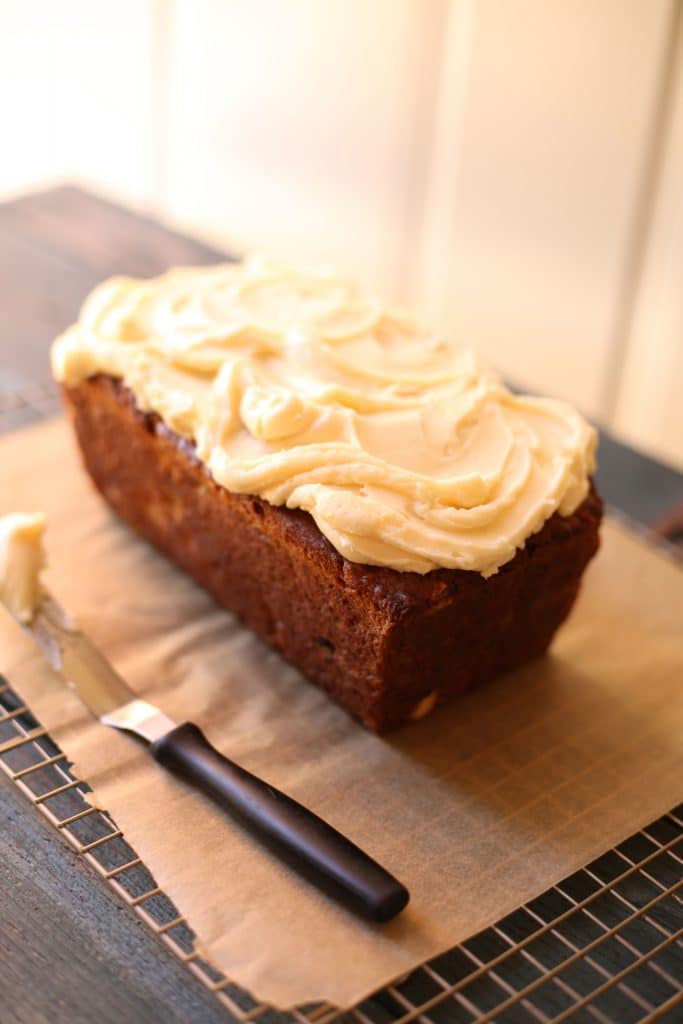 California Fig Banana Bread on a cooling rack with cream cheese frosting and a spreading knife with white background