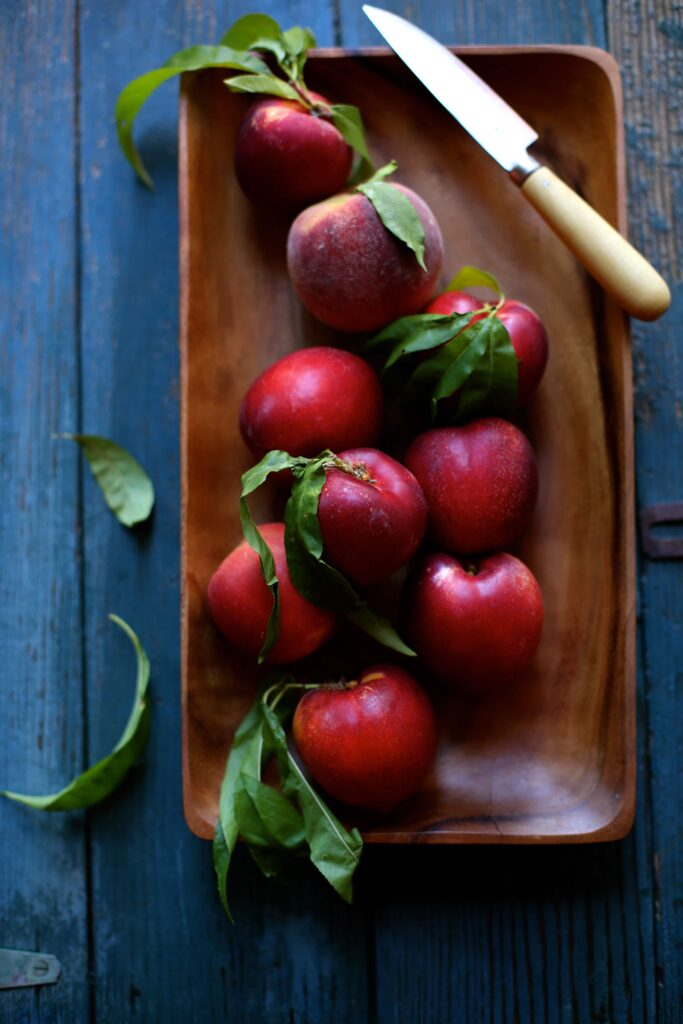 Nectarines on a wood board with knife and blue background