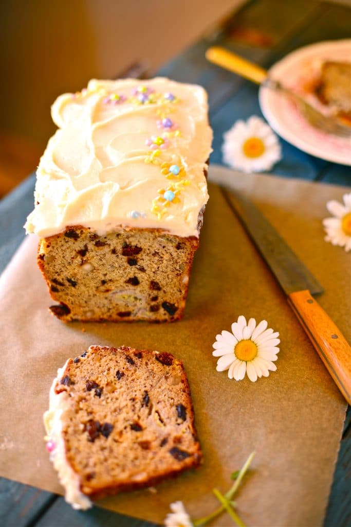 California Fig Banana Bread with daisys and a knife on a parchment paper lined blue wood board