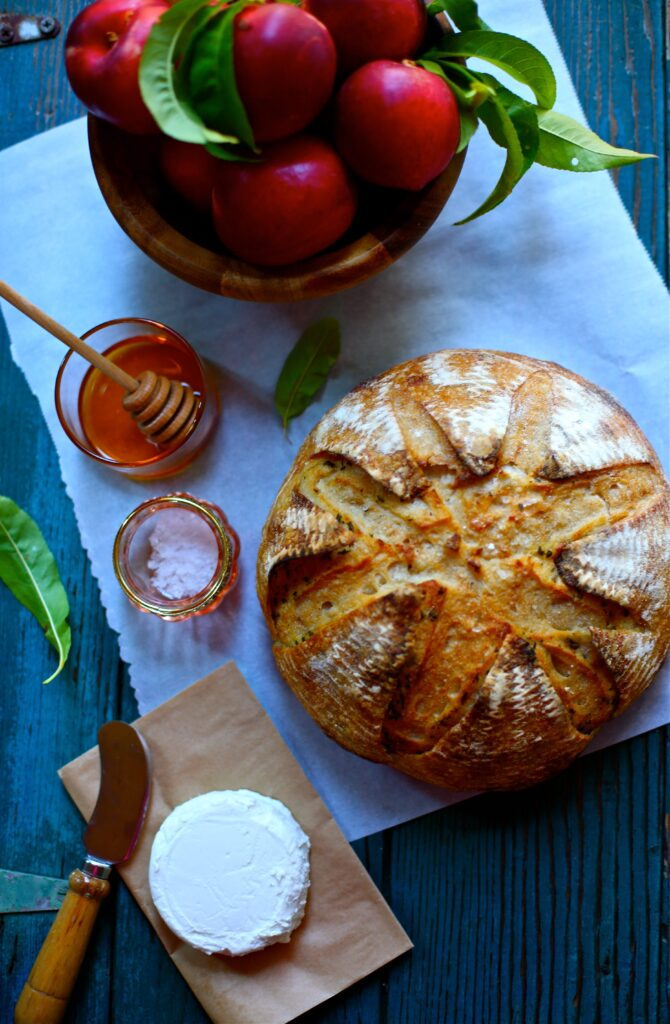 Sourdough round with a bowl of nectarines and honey and salt and goat cheese on a wood board