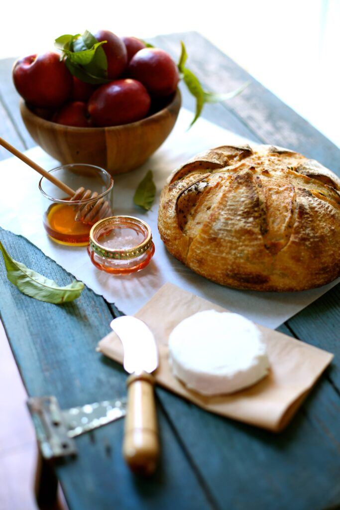Sourdough bread and a bowl of nectarines and goat cheese and knife and honey and salt