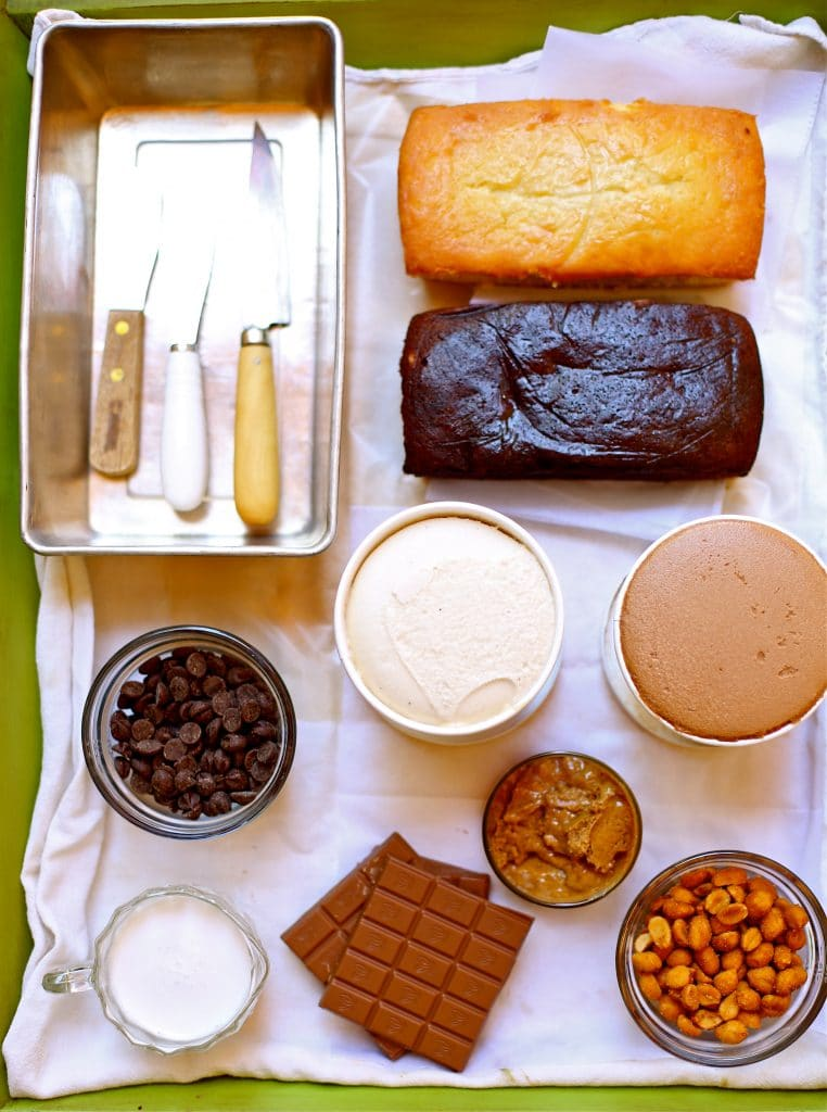 Ingredients for ice cream cake with peanut butter ganache, vanilla and chocolate cake and ice cream and chocolate and cream and knifes