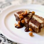 ice cream cake with peanut butter ganache on a white plate with peanuts