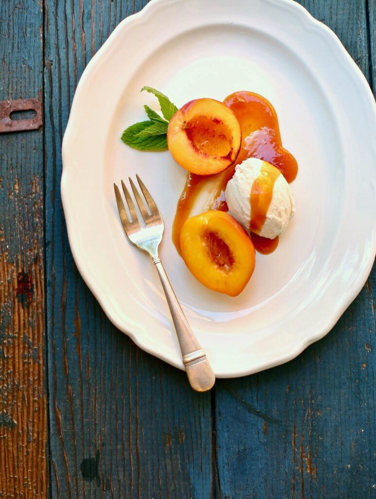 roasted nectarines on a white platter with a silver fork