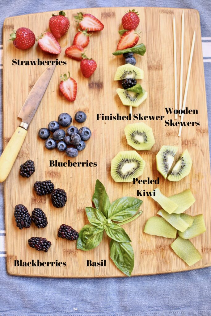 ingredients for a fruit kabob on a cutting board