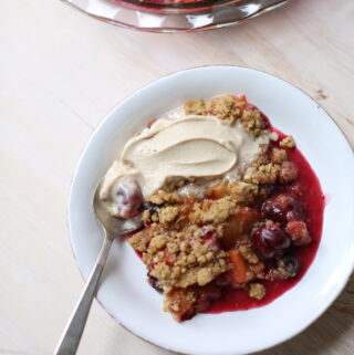 a bowl of summer fruit crisp with ice cream on a white table