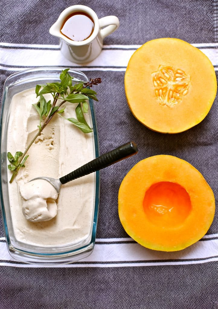 Vanilla Ice Cream and two melon halves with basil and caramel sauce on a gray and white stripedtowel