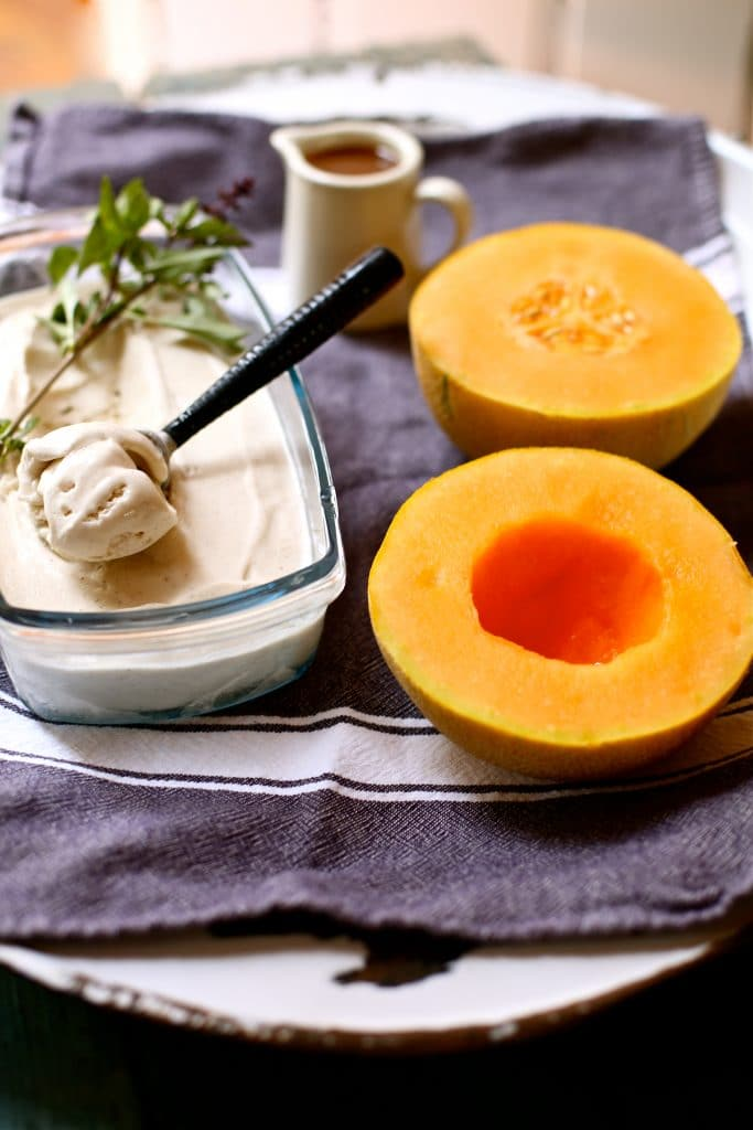 two melon halves and vanilla ice cream with a side of caramel sauce on a gray and white striped towel and white platter