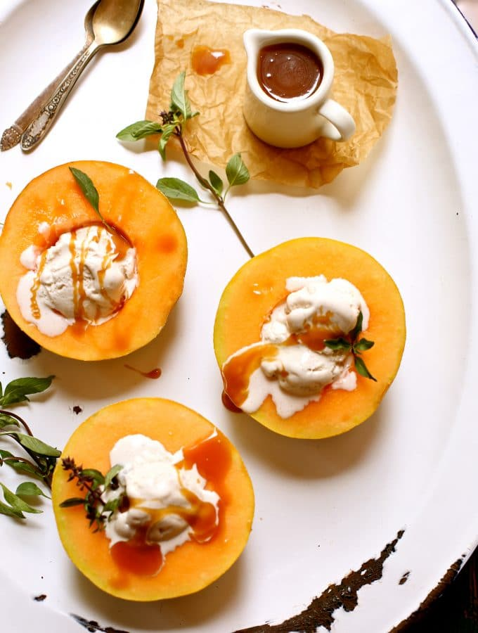 Three melons on a white platter with ice cream and caramel sauce and ice
