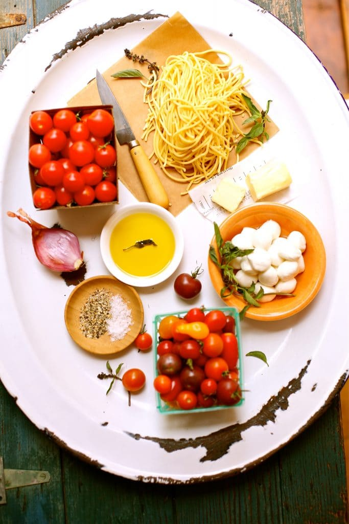 Ingredients for Summer Pasta, cherry tomatoes, olive oil, knife, shallot, mozzarella, salt and pepper and basil