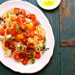 Summer Pasta of spaghetti noodles, tomatoes, mozarella and fresh basil on a blue table with olive oil on the side.