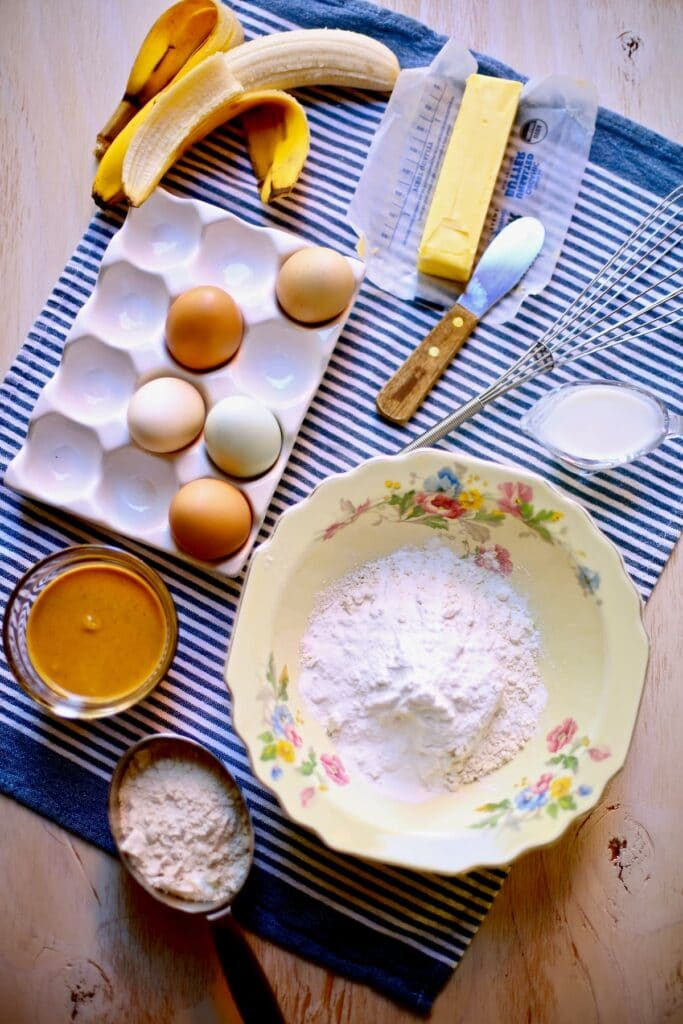 eggs, flour butter and peanut butter on a blue tablecloth with knife