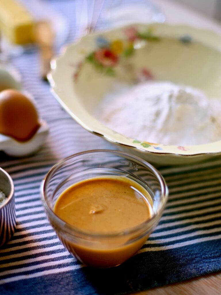 peanut butter and flour and eggs in containers on blue striped tablecloth