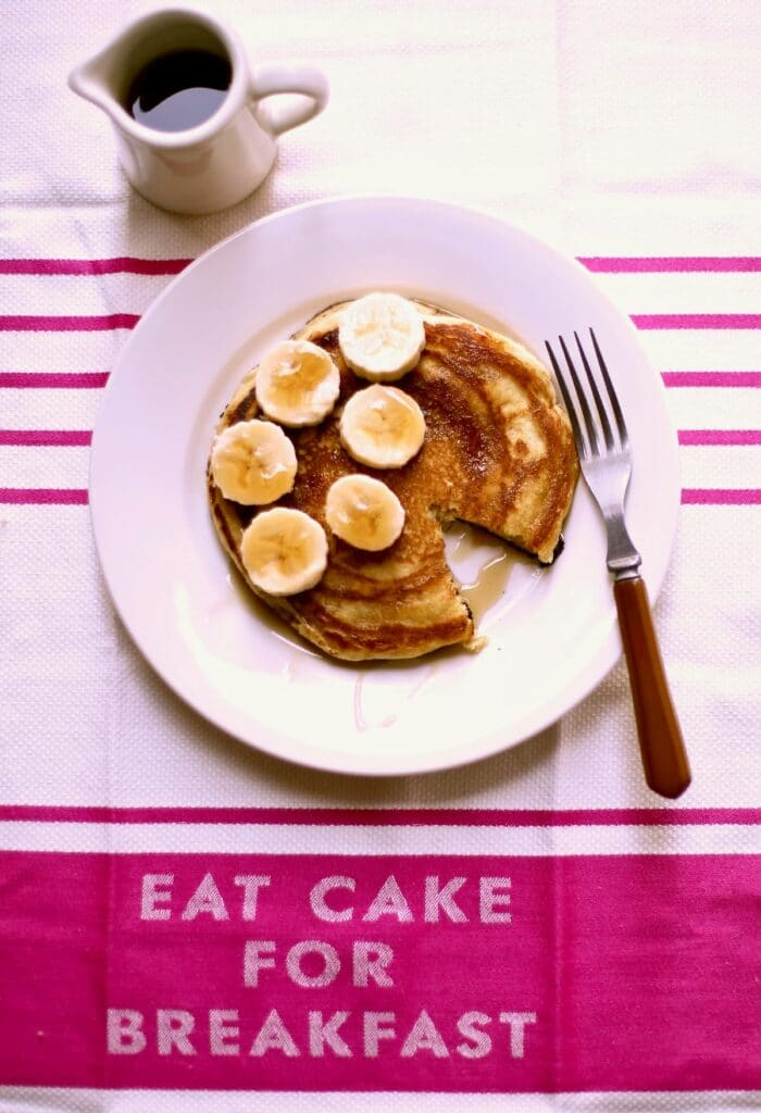 pancakes with bananas on a pink cloth with text
