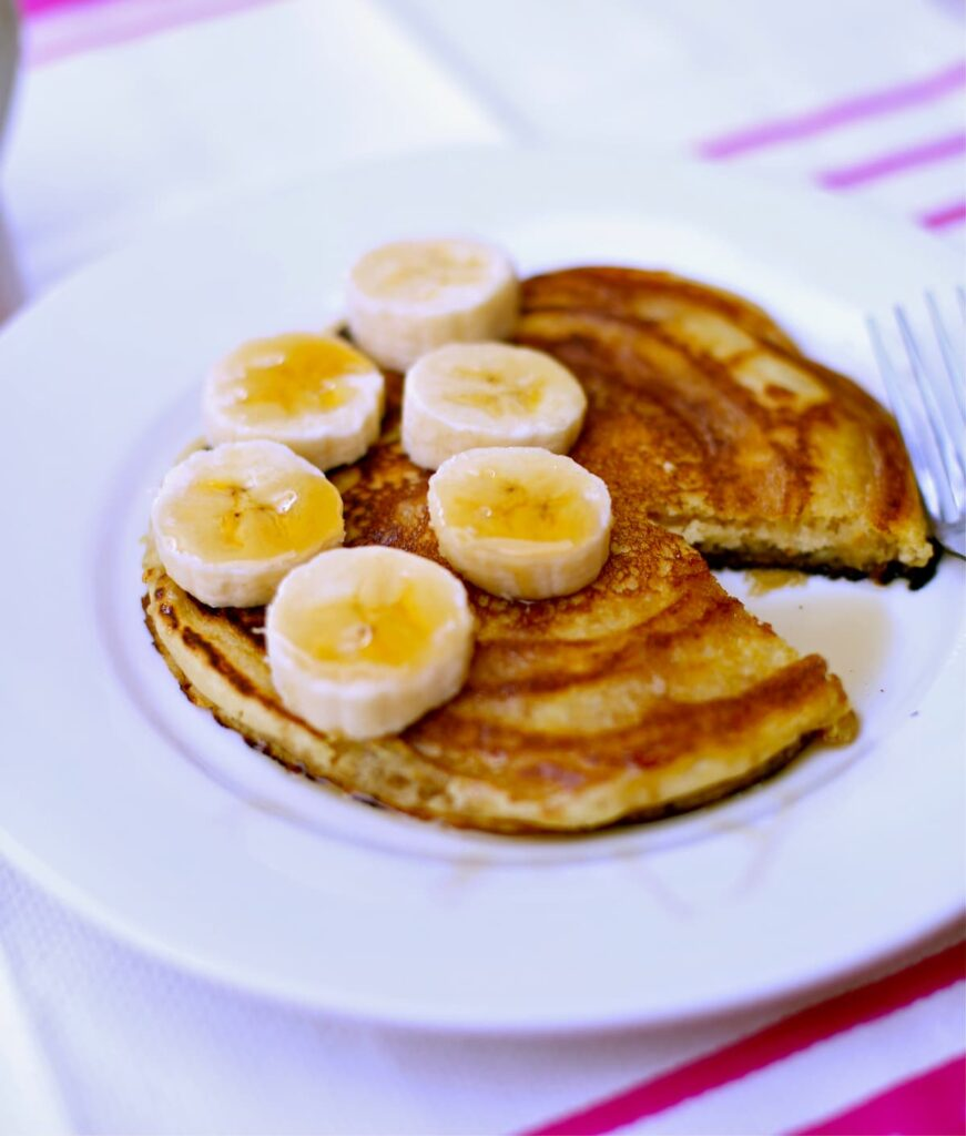 pancakes with bananas on a white plate