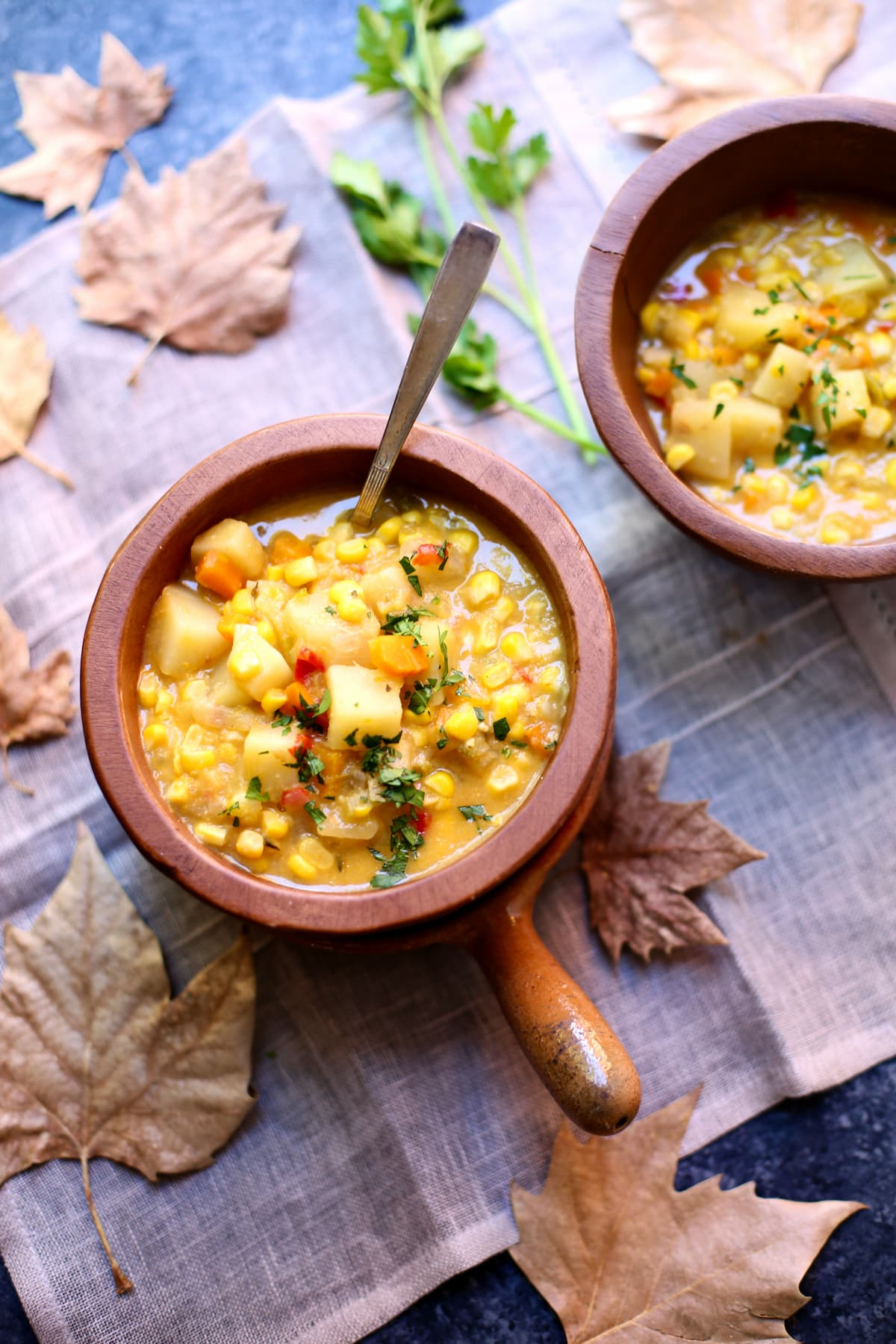 two bowls of corn soup on a table with leaves.