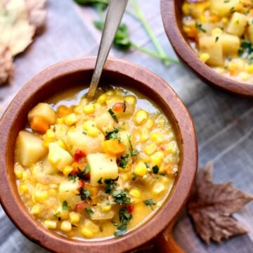 a bowl of corn chowder with a spoon in it on a table with fall leaves around it.