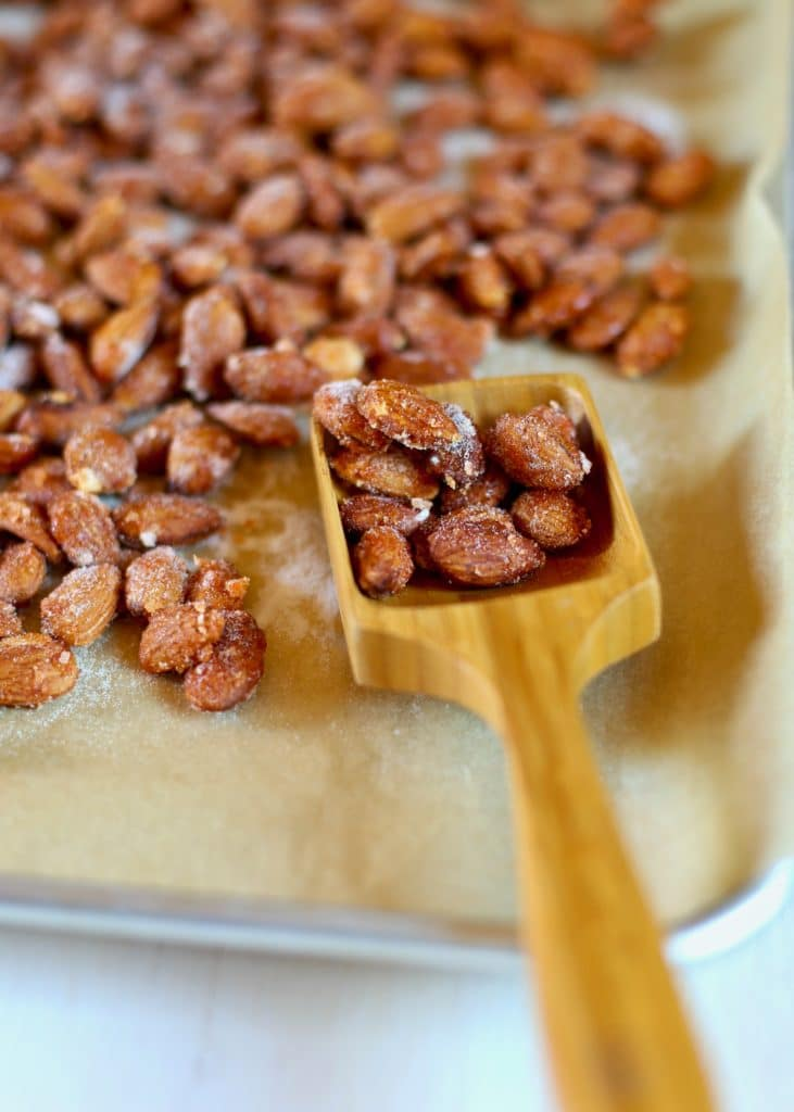 almonds that have been roasted on a baking sheet with a wooden spoon