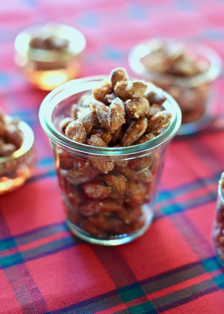 Almonds that are for snacking in a glass jar on a red tablecloth