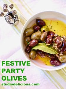 Festive Party Olives in a white bowl with silver toothpicks and green text