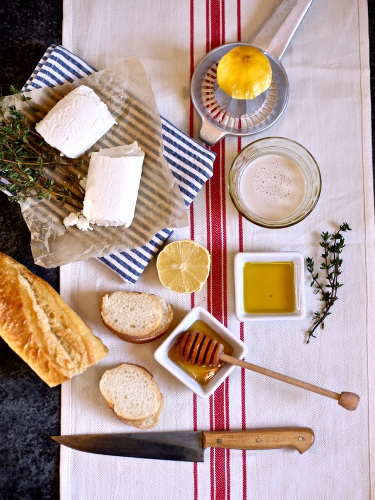 cheese, honey, thyme and bread on a white towel
