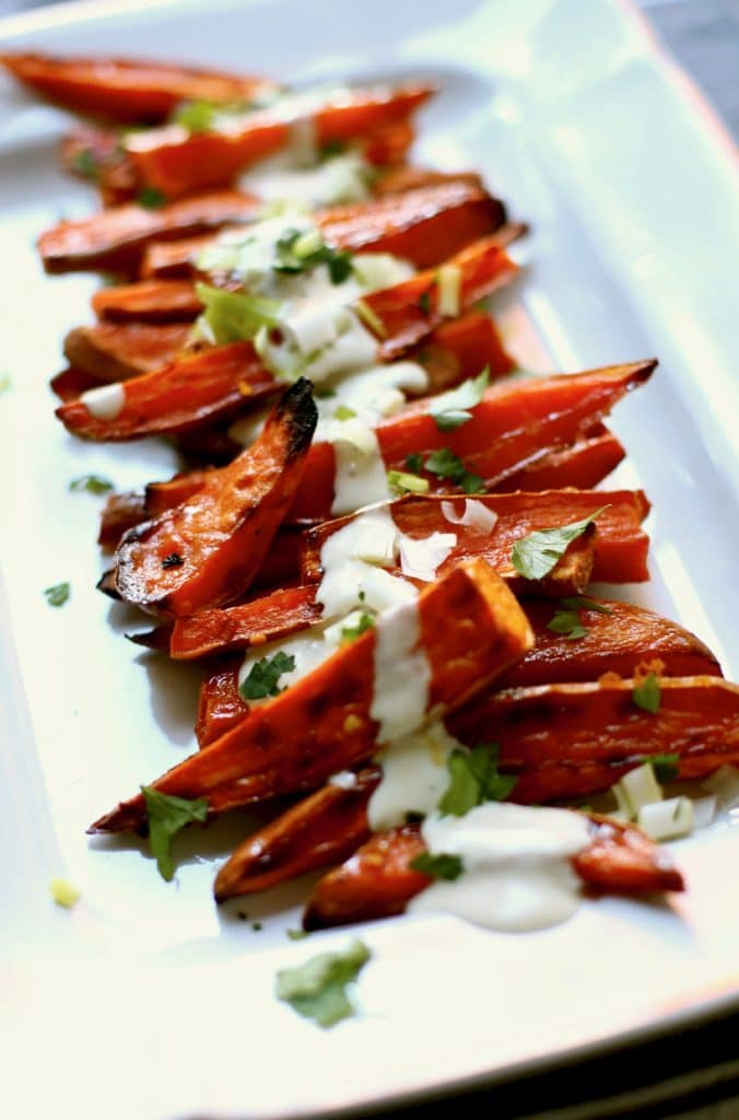 Roasted sweet potatoes on a white platter with yogurt sauce