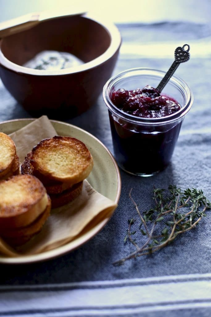 cranberry compote and toasts and thyme on a blue table
