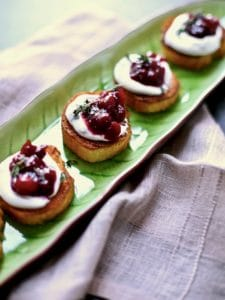 cranberry goat cheese toast appetizers on a green serving platter