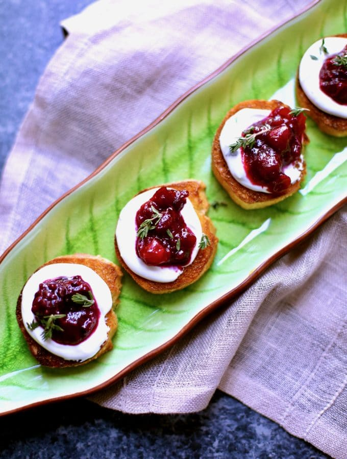goat cheese cranberry appetizer toasts on a green platter with cloth napkin background
