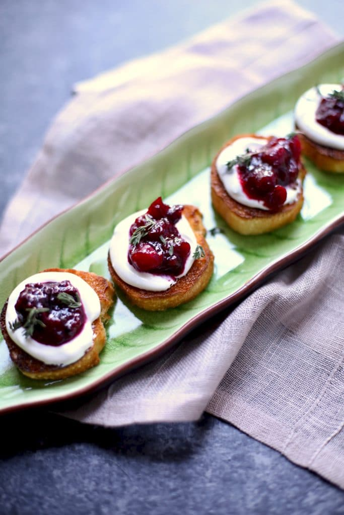 appetizer toasts with goat cheese on a green serving platter