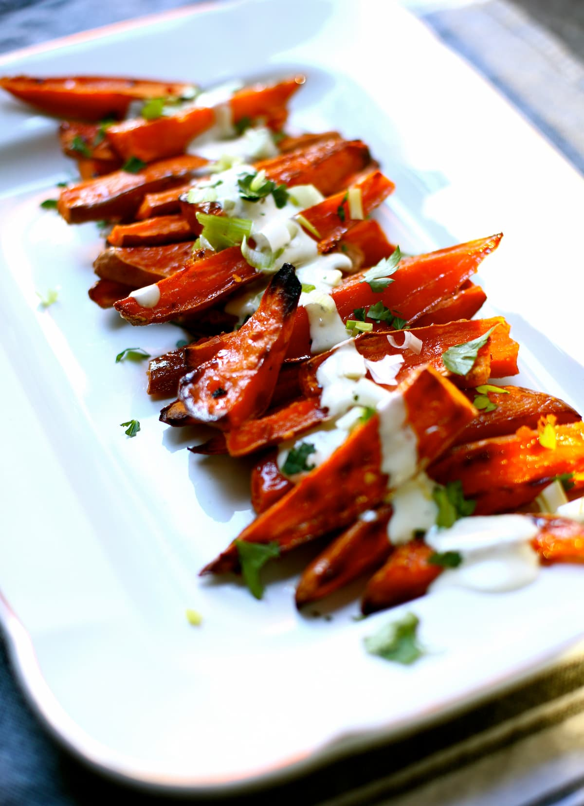 a white platter of roasted sweet potatoes.