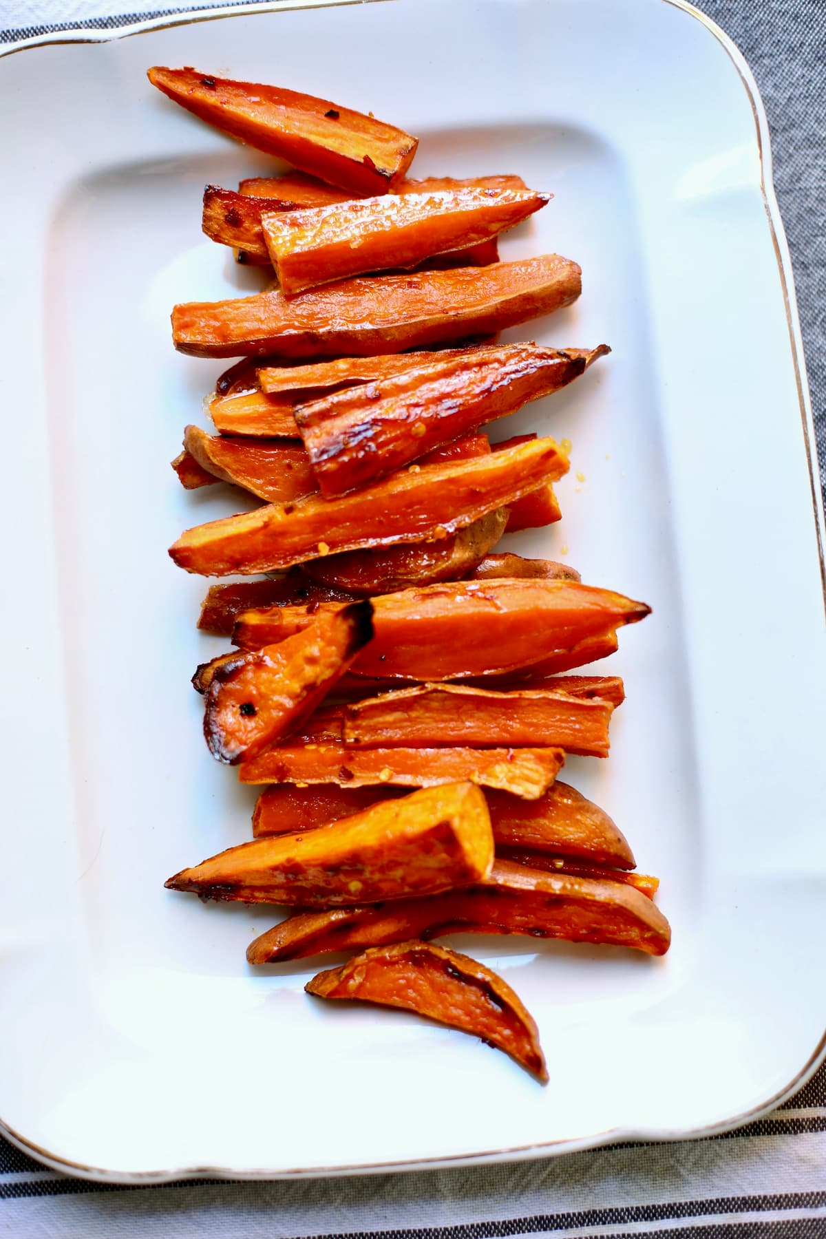 a white tray of roasted sweet potatoes.