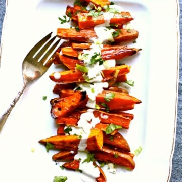 a white platter with a serving fork of roasted sweet potatoes.