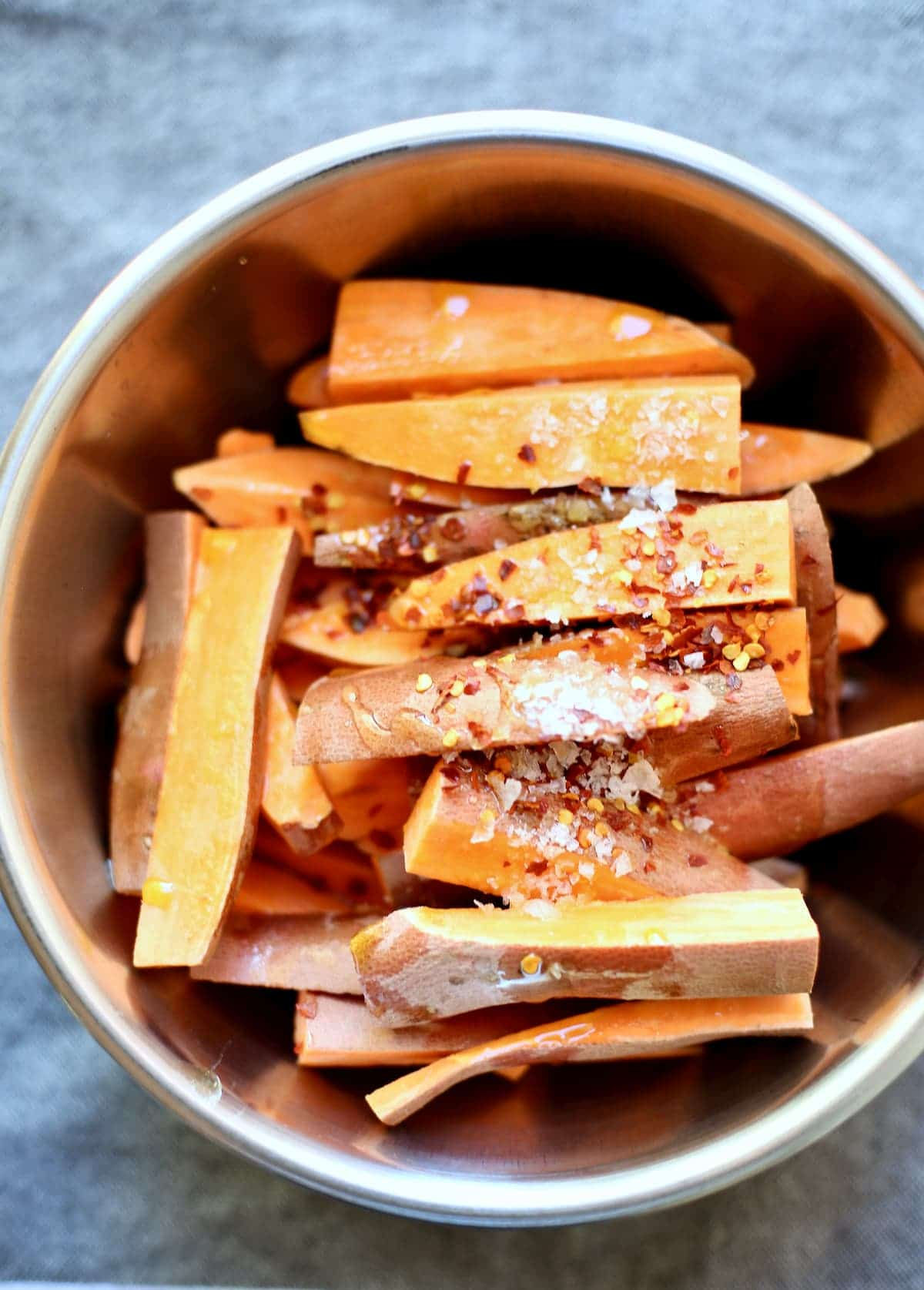 a bowl of cut and raw sweet potatoes with spices on top.