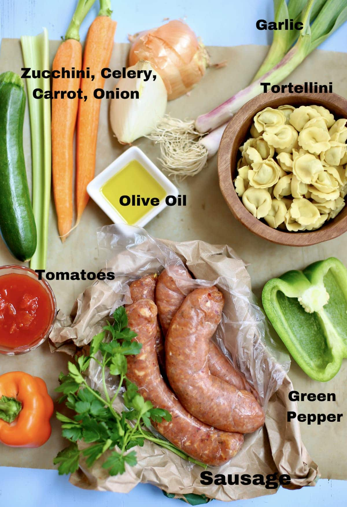 a grouping of ingredients for soup, vegeatables, tortellini and chicken sausage with a text overlay saying what the ingredients are